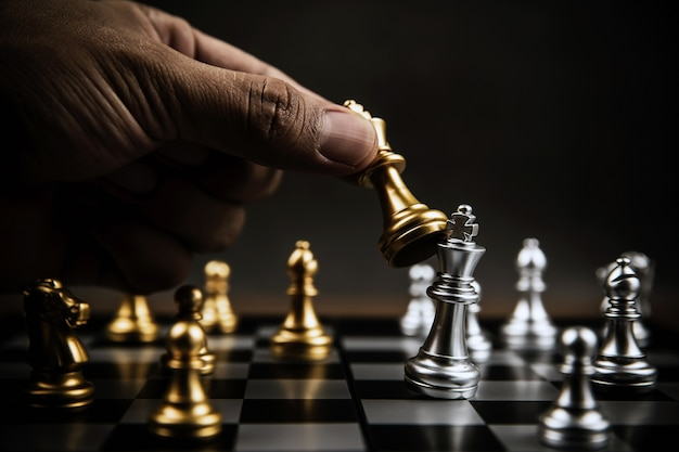Close up hand choose gold chess to fight with silver chess team on chess board Premium Photo