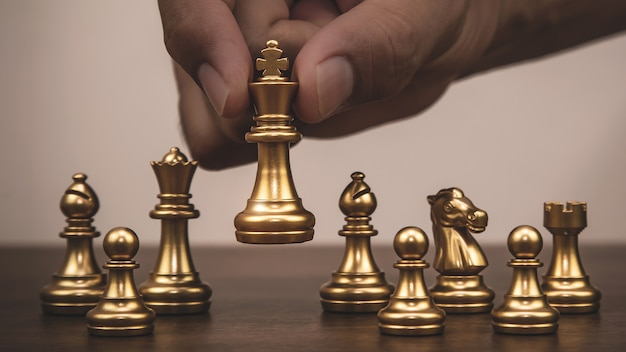 Close up hand choose king gold chess Premium Photo