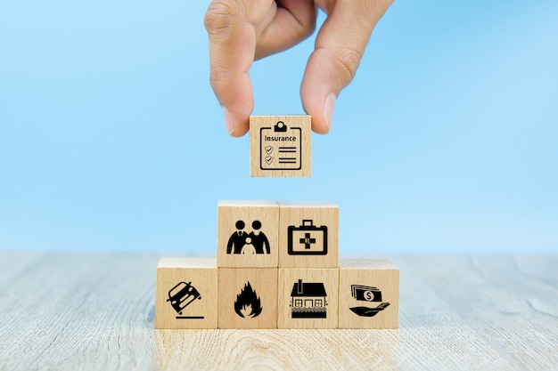 Close-up hand choose a red wooden toy blocks with insurance icon for safety family insurance Premium Photo