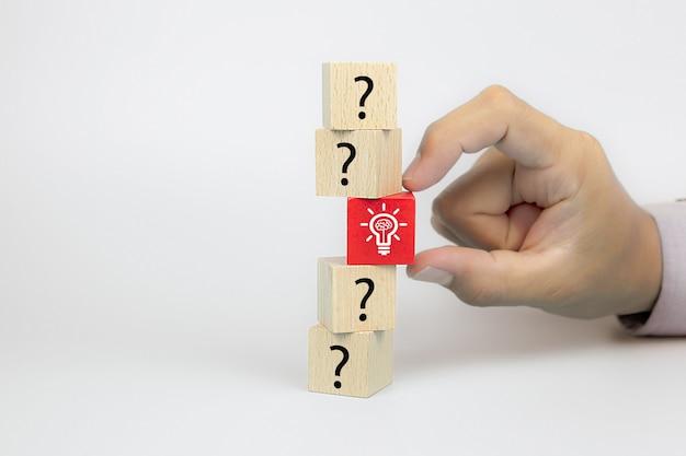 Закройте руку, выбирая значок лампочки из символа вопросительного знака на кубических деревянных игрушечных блоках Premium Фотографии