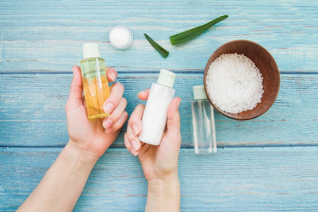 Close-up of hand choosing the natural spa spray bottle on wooden table Free Photo