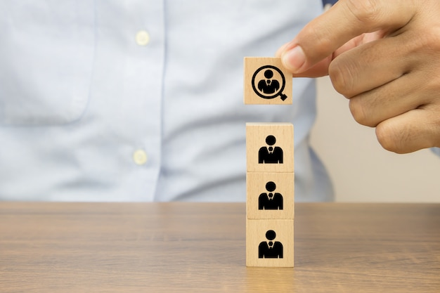 Close up hand choosing people in a magnifying glass icons on cube wooden toy blocks concepts human resources for business organizations and leadership. Premium Photo