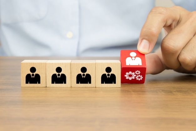 Close up hand choosing people with cog icon on cube wooden toy blocks concepts of human resources. Premium Photo
