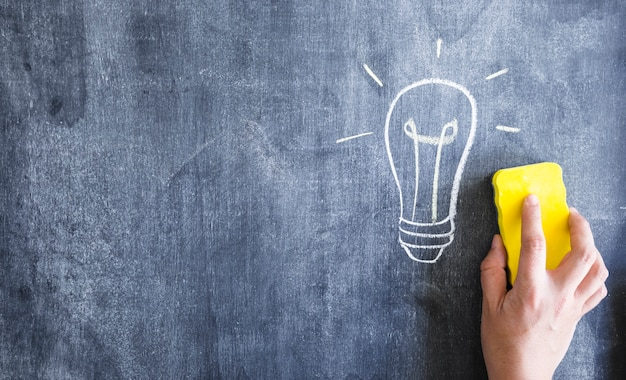 Close-up of hand cleaning the light bulb drawn on blackboard with duster Premium Photo