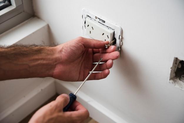 Close-up of hand fixing plug socket using screwdriver Free Photo