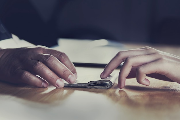 Close up hand giving money for partner on desk Premium Photo
