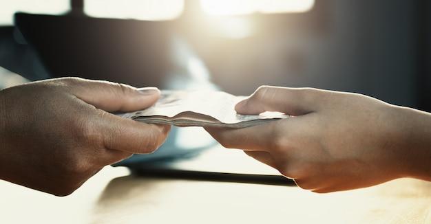 Close up hand giving money for partner on desk Premium Photo