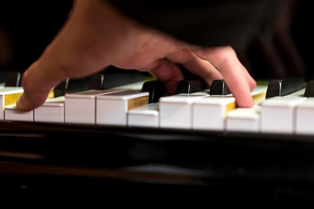 Крупным планом рука держит аккорд на фортепиано Бесплатные Фотографии