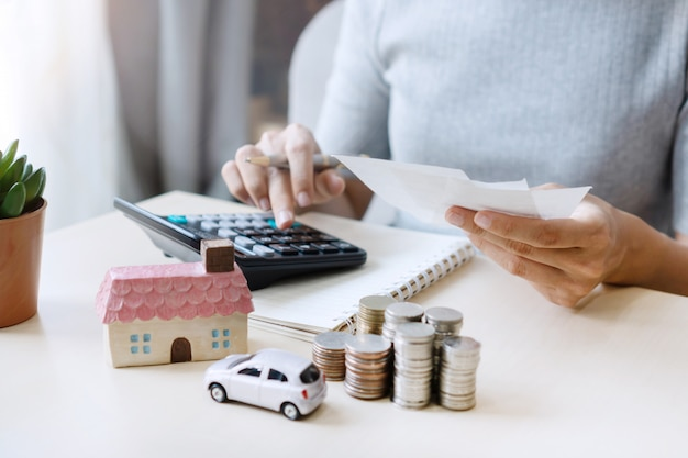 Close up of hand holding bills while using calculator, stack of coins, toy house and car on table, saving for future, manage to success,business and finance concept. Premium Photo
