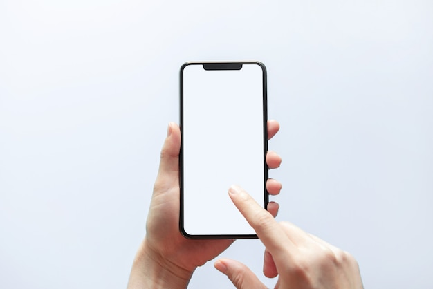 Close up hand holding black phone white screen. isolated on white wall. mobile phone frameless design concept. Premium Photo