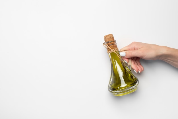 Close-up hand holding bottle of olive oil Free Photo