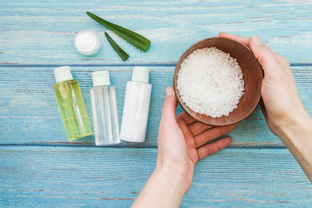 Close-up of hand holding bowl of rock salts with aloevera spray bottles and cream Free Photo