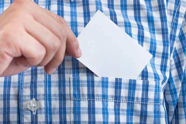 A close up of a hand holding a business card on a shirt Premium Photo