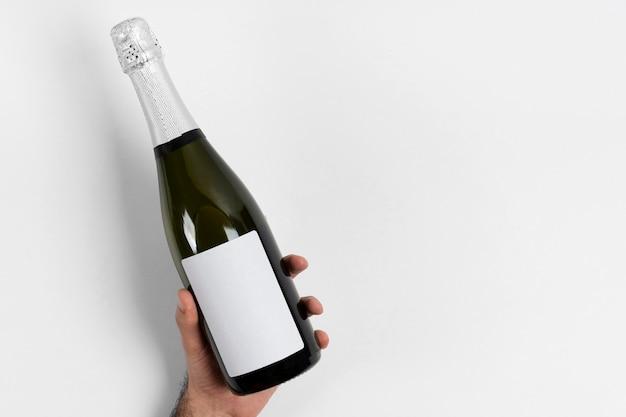 Крупным планом рука бутылка шампанского Бесплатные Фотографии