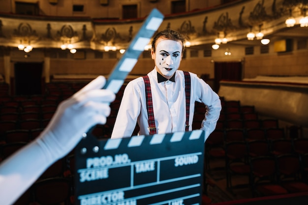 Close-up of hand holding clapperboard in front of male mime Free Photo