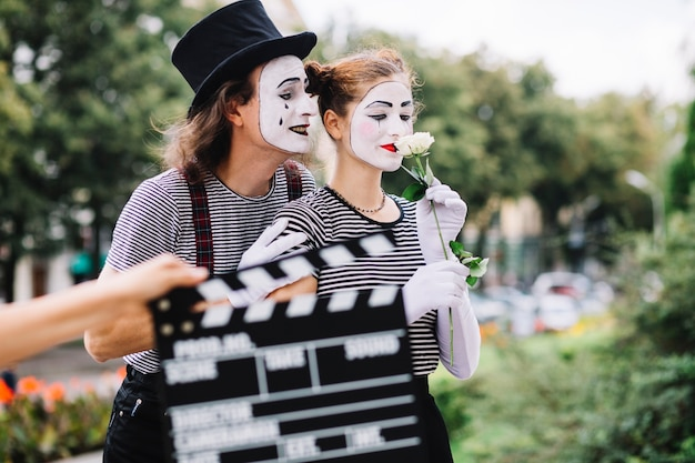 Close-up of a hand holding clapperboard in front of mime couple Free Photo