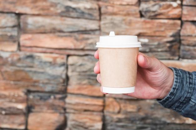 コーヒーカップを持っているクローズアップの手 無料写真
