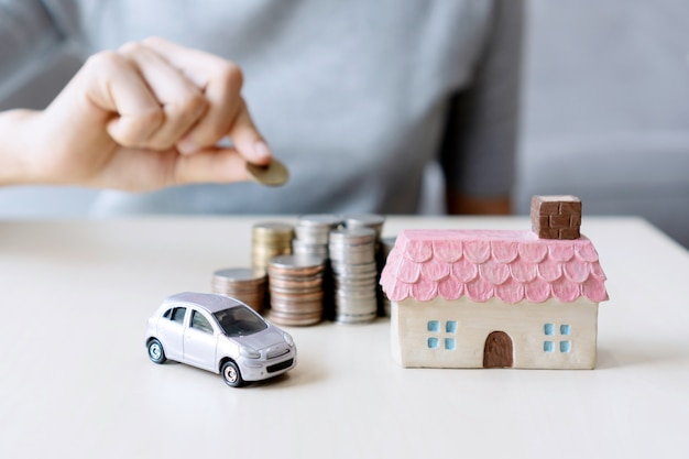 Close up hand holding coin, stack of money, toy house and car on table, saving for future, manage to success, finance concept. Premium Photo