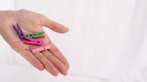 Close-up hand holding colourful clothes-pins Free Photo