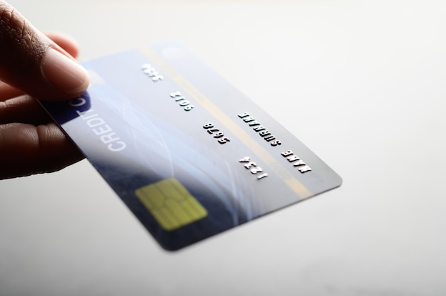 Close up of hand holding credit card Free Photo