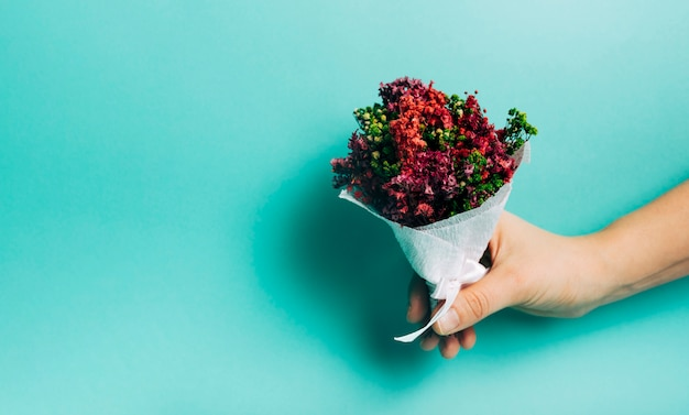 Close-up of hand holding decorative flower bouquet against turquoise background Free Photo