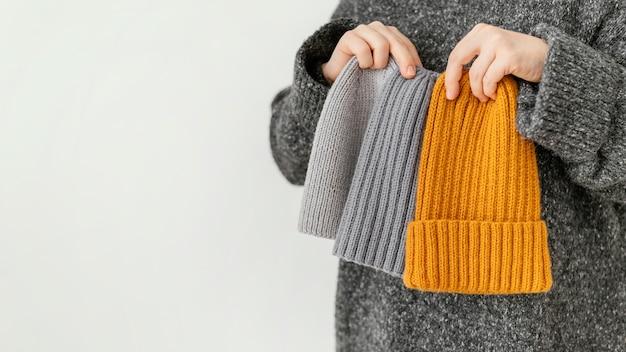 Close-up mano che tiene diversi cappelli lavorati a maglia Foto Gratuite