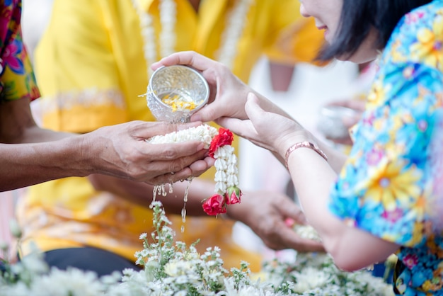 Close up hand holding flower at song-kan tradition of thailand Free Photo