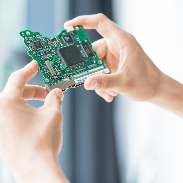 Close-up of hand holding hard disk circuit board Premium Photo