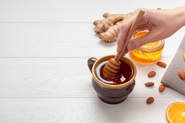 Close-up hand holding honey stick Free Photo