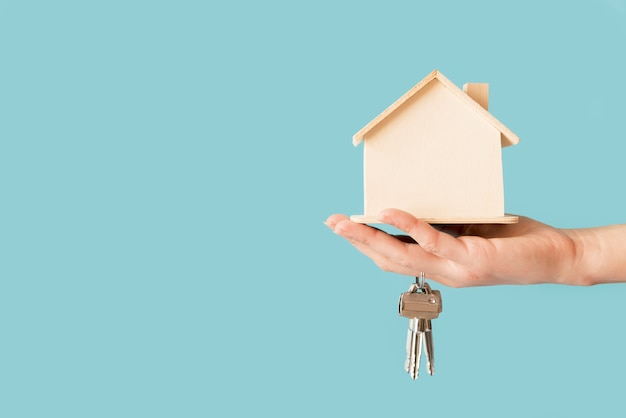 Close-up of hand holding keys and wooden house model against blue background Free Photo