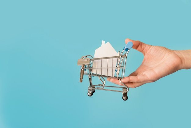 Close-up of hand holding miniature shopping cart with paper house and keys against blue background Free Photo