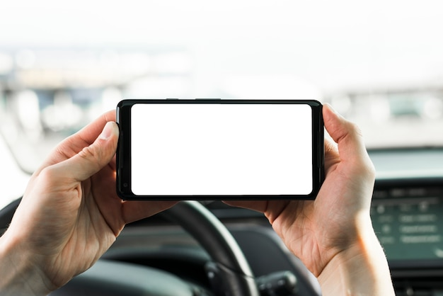 Close-up of hand holding mobile phone with blank white screen in the