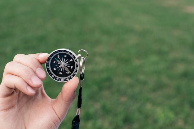 Close-up of hand holding navigational compass against green blurred background Free Photo