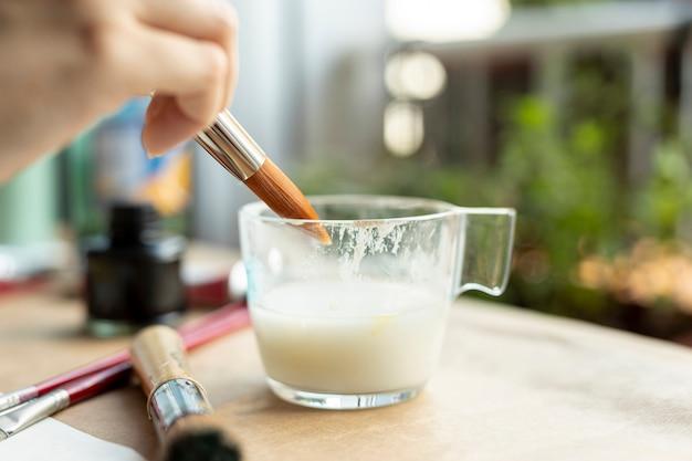 Close-up hand holding painting brush Free Photo