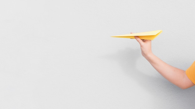 Рука крупным планом держит бумажный самолетик Бесплатные Фотографии