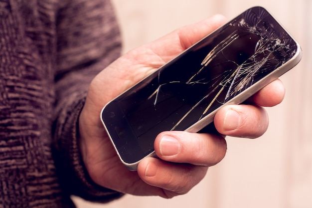 Close up on hand holding a phone with broken glass Premium Photo