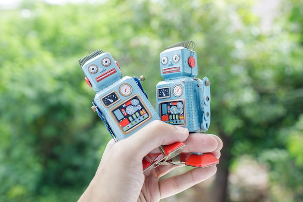 Close up on hand holding retro robot tin toy Premium Photo