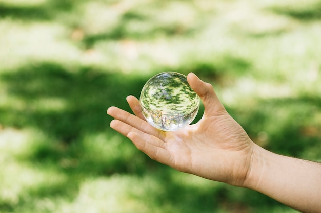 Close-up of hand holding transparent sphere at outdoors Free Photo
