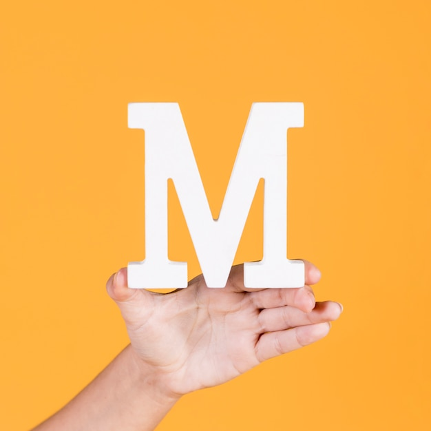 Close-up of a hand holding up the alphabet m Free Photo