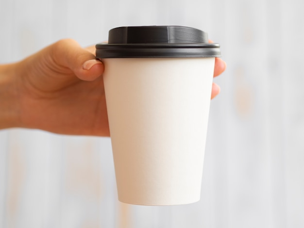 Close-up hand holding up coffee cup Free Photo