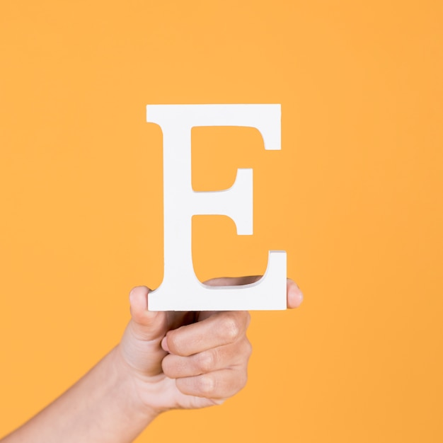 Close-up of hand holding up the uppercase capital letter e over yellow background Free Photo
