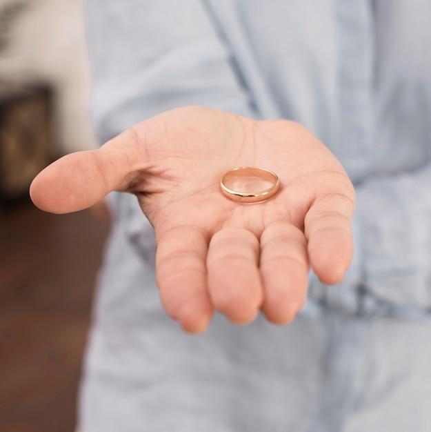 Close-up hand holding wedding ring Free Photo