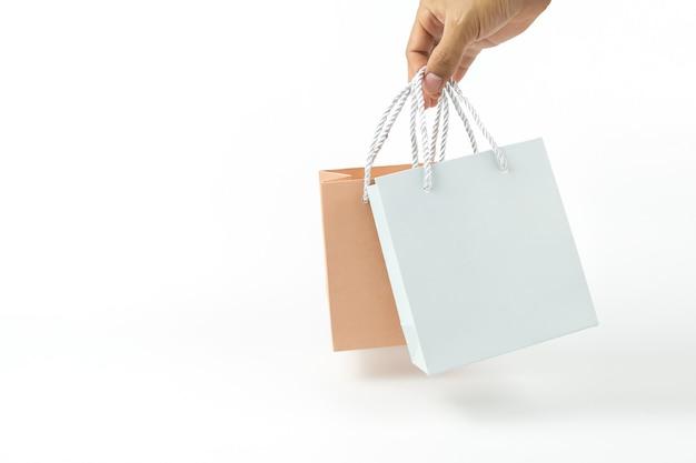 손을 가까이 흰색 빈 종이 쇼핑백을 들고있다 프리미엄 사진