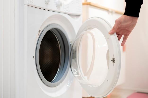 Close up hand launch set and start washing machine laundry at home bathroom Premium Photo