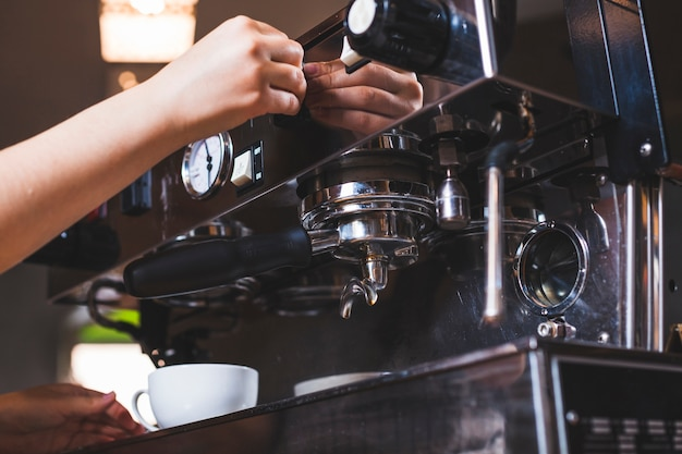 Close-up of hand making coffee in coffee shop Free Photo
