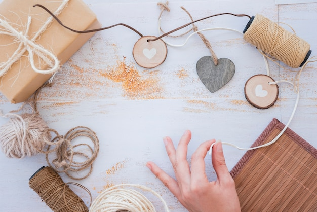Close-up of hand making heart garland with spool and wrapped gift box on white desk Free Photo