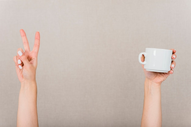 Close-up of hand making peace gesture and white cup against colored backdrop Free Photo