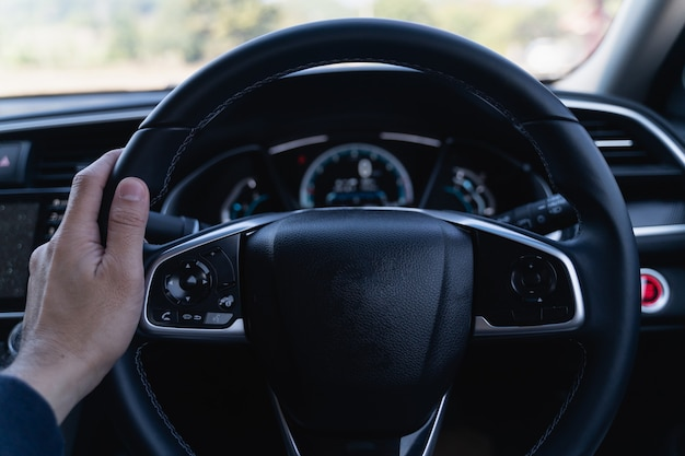 Close up of hand man holding steering wheel in the modern car Premium Photo
