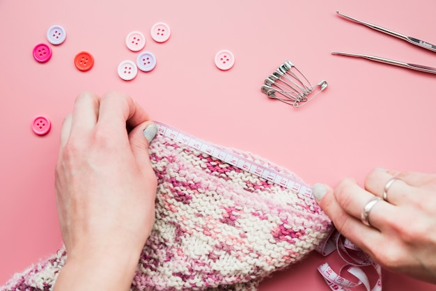 Close-up of hand measuring the knitted fabric with tape on pink background Free Photo