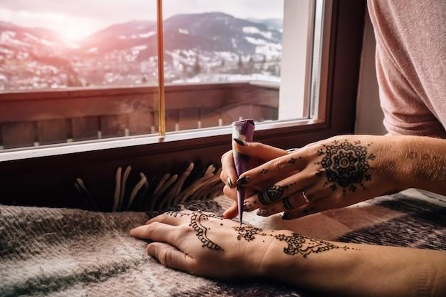 Close Up Of Hand Mehndi Body Art On Winter Landscape Premium Photo